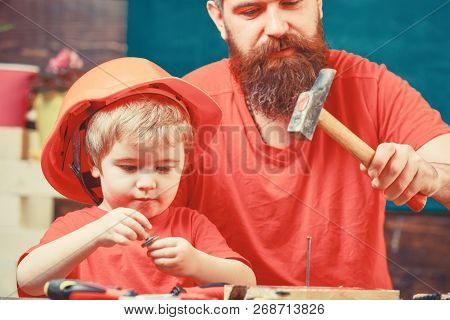 Masculine Duties Concept. Father, Parent With Beard Teaching Little Son To Use Hobnails And Hammer.