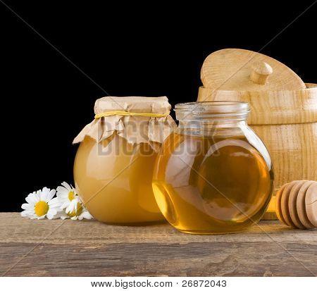 honey and flowers isolated on black background