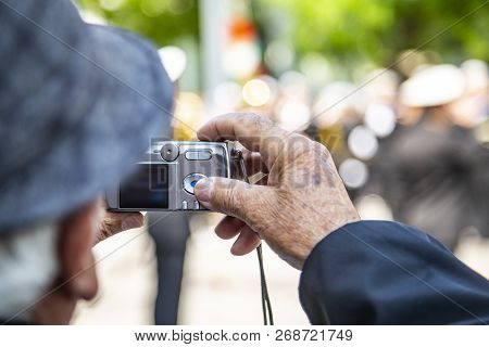Old Man With A Hat Holding An Old Camera And Shooting In The City. An Old Camera Model In The Hands