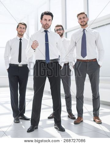 in full growth.confident businessman standing in front of his business team