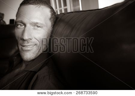 Attractive Middle Aged Man Wearing Black Shirt And Sitting On Sofa Looking At Camera