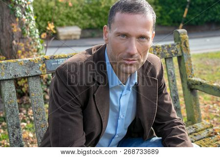 Handsome Middle Aged Man Wearing Shirt And Jacket Sitting On Park Bench