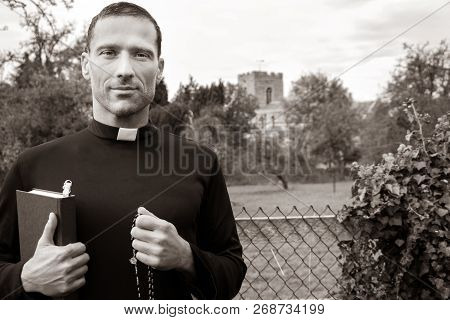 Good Looking Priest Stands In Front Of Fence To Field With Church In Background