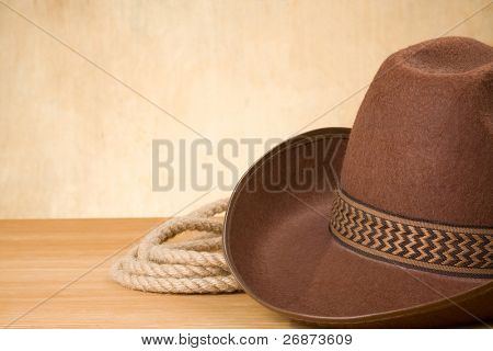 brown cowboy hat and rope on wood texture background