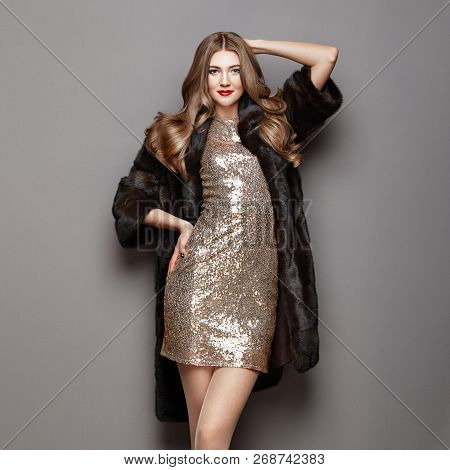 Fashion Portrait Young Woman In Black Fur Coat. Girl With Elegant Hairstyle Posing On A Gray Backgro