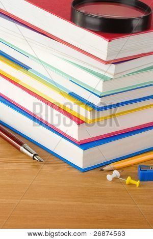 pile of new book and pens on wood background texture