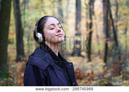 Young Woman In Her 20s Listening To Music With Wireless Headphones In Forest - Candid Outdoor Lifest