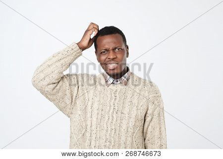 Young African Man In Sweater Thinking Scratching Head On White Background