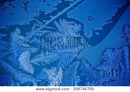 Beautiful Frosty Pattern On A Winter Window Close Up. Frozen Pattern On The Window. Frozen Water On