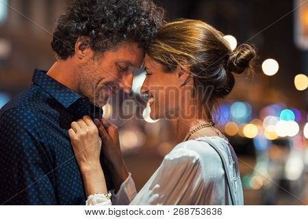 Romantic man and woman on evening date. Happy husband and smiling wife embracing touching head to head on city street at night. Mature couple loving during a romantic night.