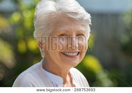 Portrait of serene old woman in garden looking at camera. Closeup portrait of happy older beautiful woman standing outside in summer and smiling. Happy retired senior woman relaxing outdoor.