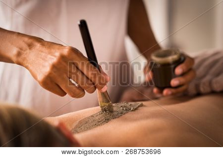 Closeup of beautician applying clay with brush on back of woman lying on massage table at spa. Hands using brush for clay mask. Lady receiving a scrub exfoliation therapy on body in a wellness centre.