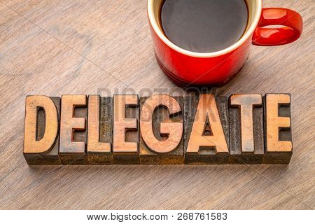 delegate - word abstract in vintage letterpress wood type with a cup of coffee
