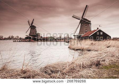 Wooden Windmills On Zaan River Coast, Zaanse Schans Town, Popular Tourist Attractions Of The Netherl