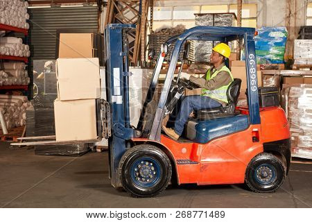 Forklift driver transports cargo by forklift in warehouse