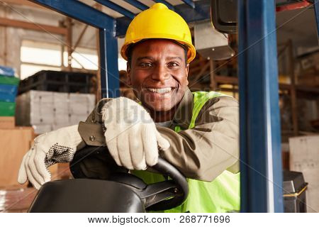 African logistics man as a forklift driver in the warehouse of a freight forwarder
