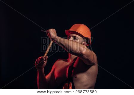 Site Is Under Construction. Man Work With Hammer. Muscular Man Builder At Work Under Construction. H