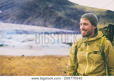 Winter hike on snow mountain happy hiker man walking in ice wilderness in Iceland . Europe travel adventure trek in nature landscape. Person wearing hat and jacket for cold weather, bag, hiking poles.