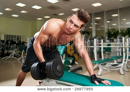 Muscular man working his biceps with heavy dumbbells