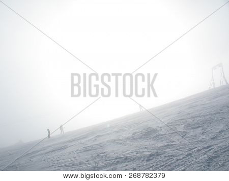 Icy Ski Lift With Inexperienced Skier In In Thick Fog. Steep Slope In The Fog On A Snowy Mountain.