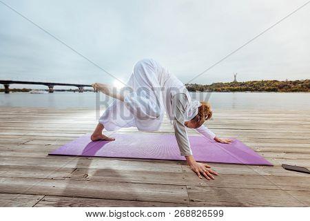 Woman Practising Yoga Poses While Doing Morning Exercies