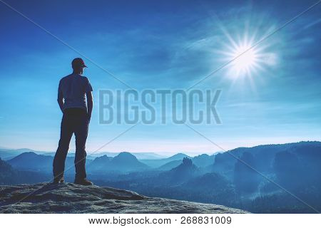 Man Walking On The Edge Of A Cliff High Above Misty Valley.  Travel Hiking And Lifestyle. Personal S