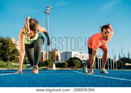 Athlete couple at starting position ready to start a race. Sprinters ready for race on race track. Happy and strong woman against man. poster
