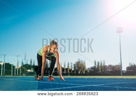 Young athlete woman at starting position ready to start a race. Sprinters ready for race on race track. poster