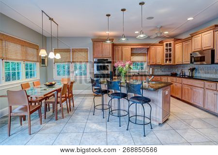 Open concept kitchen and dining room combination with windows