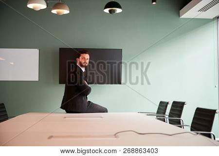 Portrait Of Young Businessman Sitting On Boardroom Table At Graduate Recruitment Assessment Day In Office