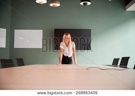 Portrait Of Young Businesswoman Leaning On Boardroom Table At Graduate Recruitment Assessment Day In Office