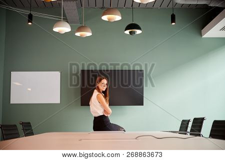 Portrait Of Young Businesswoman Sitting On Boardroom Table At Graduate Recruitment Assessment Day In Office