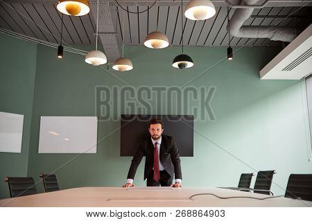 Portrait Of Young Businessman Leaning On Boardroom Table At Graduate Recruitment Assessment Day In Office