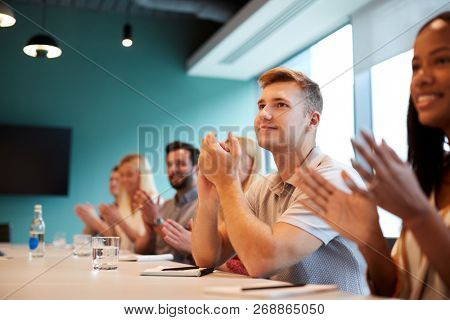 Group Of Young Candidates Sitting At Boardroom Table Applauding Presentation At Business Graduate Recruitment Assessment Day