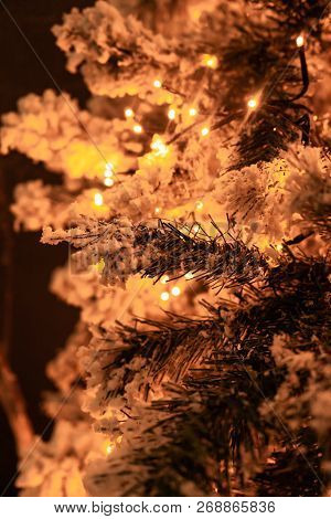 Festive White Flocked Christmas Tree With String Of Lights And Glowing Background With Copy Space