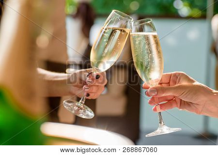 Two Girls Clink Glasses Of Champagne On A Beautiful Summer Terrace. Sparkling Champagne Glasses
