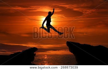 Freedom, Risk, Challenge And Success. Man Jumping Over Precipice Between Two Rocky Mountains At Suns