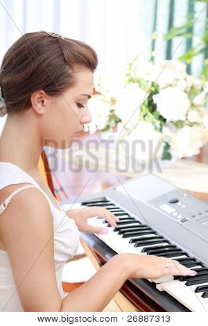 Young beautiful Caucasian woman playing on electric piano