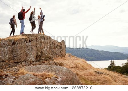 A group of five happy young adult friends cheer with their arms in the air at the summit during mountain hike