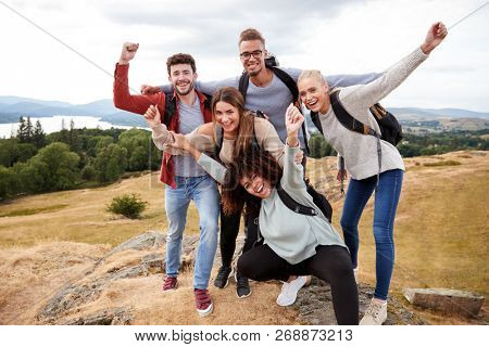 A group of five happy young adult friends cheer at the summit during mountain hike