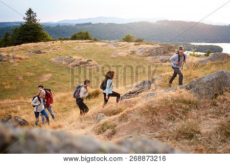 A multi ethnic group  of five young adult friends smile while climbing to the summit during a mountain hike, side view poster