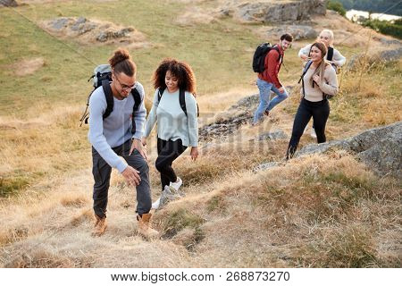 A multi ethnic group  of five young adult friends smile while climbing to the summit during a mountain hike, close up poster