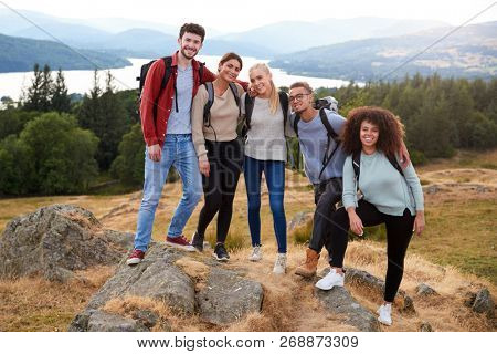 Multi ethnic group of five young adult friends standing at the summit after a mountain hike, front view
