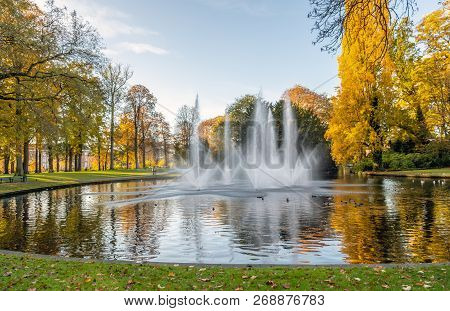 Squirting Fountains In The Pond Of The Valkenberg Park In The Dutch City Of Breda In The Fall Season