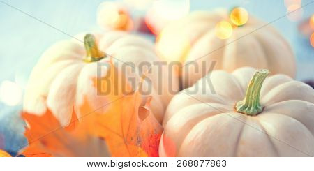 Thanksgiving Day Dinner, Served holiday table decorated with pumpkins, colorful autumn leaves and candles. Thanksgiving background, beautiful table setting