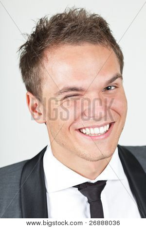 A young businessman, looking satisfied, giving a wink