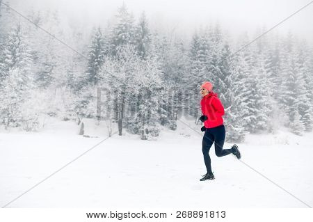 Girl Running On Snow In Winter Mountains. Sport, Fitness Inspiration And Motivation. Young Happy Wom