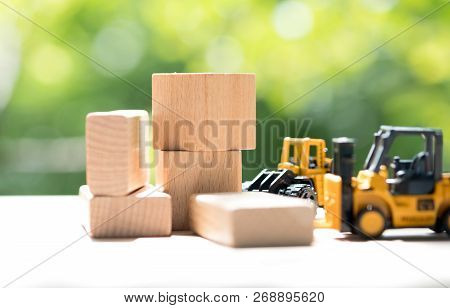 Mini Forklift Truck Load Wooden Block To Complete Building With Natural Green Background. Industry C