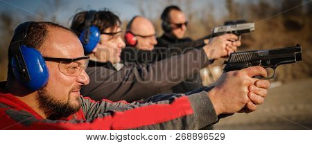 Group Of People Practice Gun Shoot On Target On Outdoor Shooting Range. Civilian Team Weapons Traini