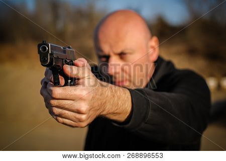 Police agent and bodyguard pointing pistol to protect from attacker. Gun point aiming front view outdoor poster